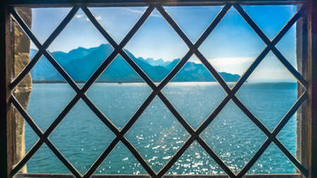 View of the blue lake and the hills from the window with bars. The metal rods are intertwined in the form of rhombs. The concept of unfreedom. Inaccessible beauty.