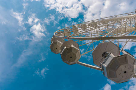Empty ferris wheel under a bright blue sky with small white clouds. Bottom view. The idea of a new day, the beginning.