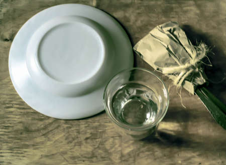 The inverted white plate, spoon and fork are tied in a case. Glass with clear water. Concept of voluntary refusal of food. Black and white image with a green tint.
