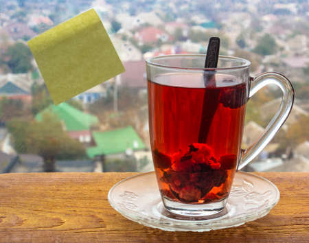 Glass cup with red fruit tea on a wooden board on the window. A yellow sticker for notes is glued on the glass. Behind glass blurred city background. Template.