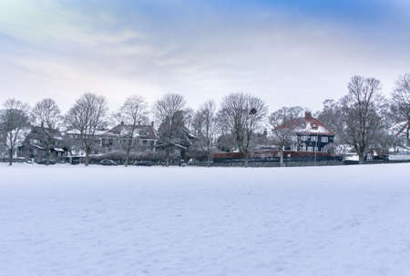 Large area covered with snow. On the horizon is a street with houses decorated for the holiday. A typical Scandinavian landscape in December.