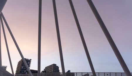 View through the metal bars of a bridge at pink sunset and modern buildings. An element of a modern pedestrian bridge. Stock Photo