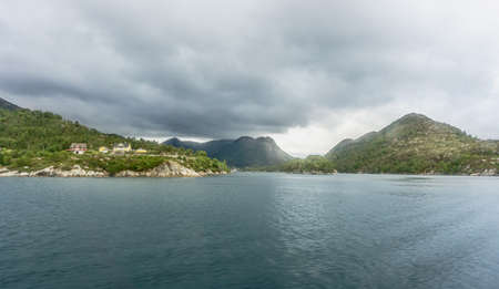 Scenic view of the surrounding shipping Norwegian fjords.View from the ferry to the green and rocky shores of Sognefjord, the longest fjord in the world. 스톡 콘텐츠
