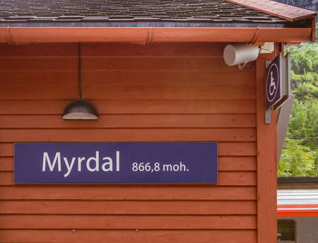 On a red wooden building there is an inscription with the name of the station and the height above sea level. MYRDAL STATION,Norway.