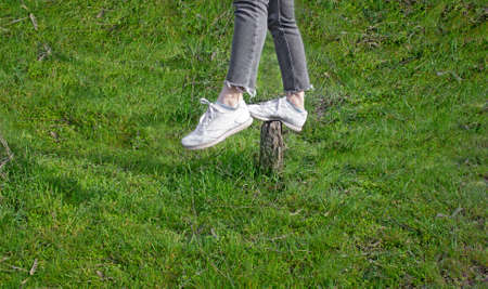 Legs in sneakers stand on an old stump among a bright green meadow. The concept of maintaining balance in any situation. Large free space.