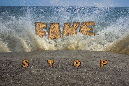 """High sea waves are breaking on a concrete pier. Close-up. There are inscriptions """"STOP"""", """"false"""", """"News"""". The concept of the fight against disinformation."""