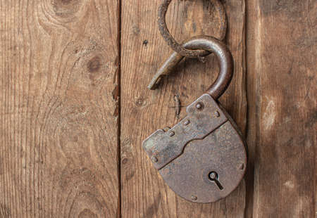 An old, rusty lock hangs open and without keys on a door hinge.