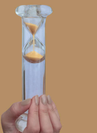 The glass hourglass is positioned vertically in the girl's hand. Isolated background. The concept of saving time and respecting the fast-paced time