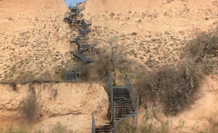 A steep metal staircase along a vertical yellow-brown clay slope, a small piece of blue sky at the very top of the slope. Fast and hard lifting concept.