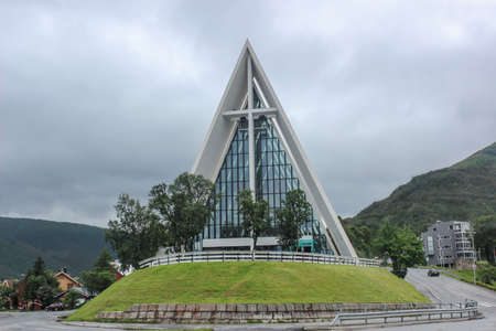 The church, which looks like a large ice triangle, is located on a low green hill. Unique architecture of cult buildings of the Scandinavian countries