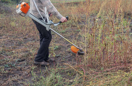 A worker cuts huge weeds with a brush cutter. The figure of a farmer holding a trimer. Side view. Close-up of weeds in a yard or field. Small viewing angle.