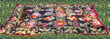 The carpet dated 1890 is set against a background of green grass. Low viewing angle and wavy edges. Hand woven rug with red, yellow, blue and other colors. Hand woven carpet with abstract design. Colorful carpet.