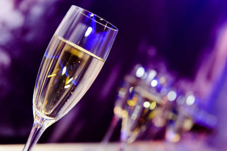 Luxury party champagne glass in nightclub neon lilac, blue and purple lights, blurry closeup
