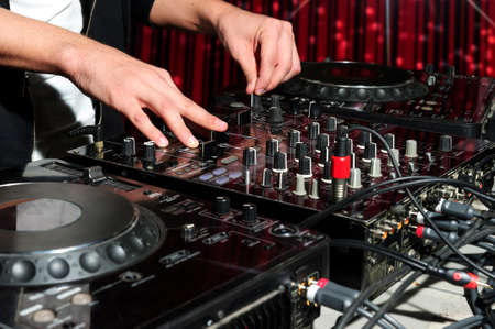 dj: DJ at dance party mixes track on sound mixer, nightclub with striped red interior, professional stereo electronic equipment Stock Photo