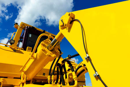 Bulldozer, huge yellow powerful construction machine with big bucket, focused on hydraulic piston arm, blue sky and white clouds on background