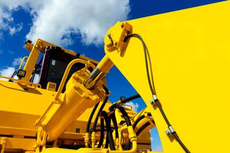 équipement: Bulldozer, énorme machine de construction puissante jaune avec grand seau, axée sur le bras de piston hydraulique, ciel bleu et nuages ??blancs sur fond Banque d'images