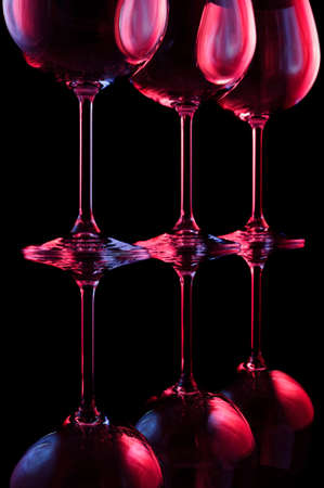 wine drinking: Nightclub wine glasses lit by red, blue, lilac party lights isolated on black background, object in row, nightlife abstraction Stock Photo