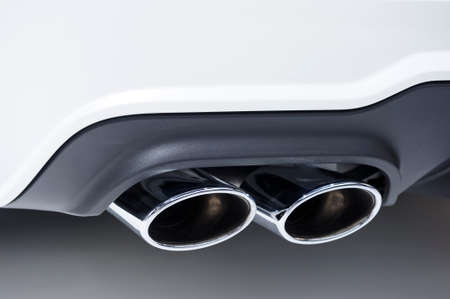 car exhaust: Double chrome exhaust pipe of powerful sport car with white bodywork and grey plastic details