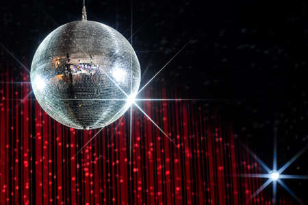 Disco ball with stars in nightclub with striped red and black walls lit by spotlight Stockfoto