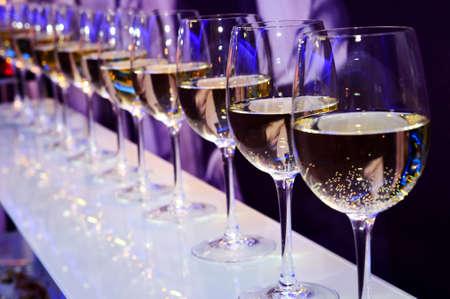 Nightclub wine glasses with white wine lit by party festive lights on dark-purple background, nightlife