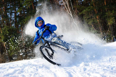 adventure travel: Cyclist extreme riding mountain bike in flying snow near winter forest in sunny cold day