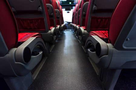 Asientos de autobús en fila con cuero rojo y revestimiento textil, apoyabrazos de madera y soportes de los cinturones de seguridad, de visión trasera, interior cómodo transporte turístico moderno, atención selectiva