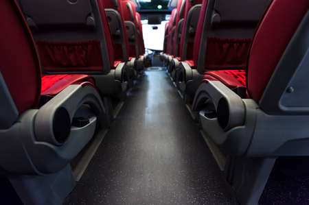 Bus seats in row with red leather and textile coating, wooden armrests and mounts for safety belts, rear view, modern comfortable tourist transport interior, selective focus Stock Photo