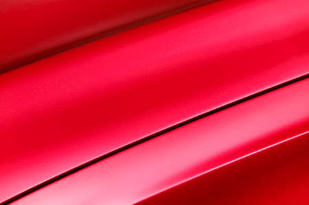 Fragment of red steel car bodywork, vehicle silver paint coating texture, selective focus, abstract