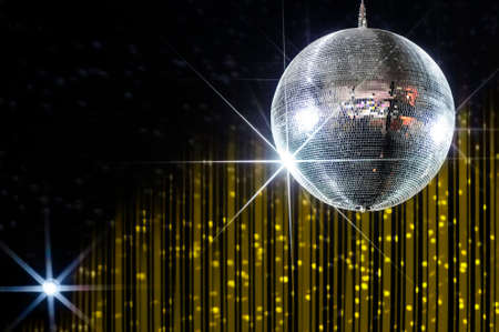Disco ball with stars in nightclub with striped yellow and black walls lit by spotlight, party and nightlife entertainment industry Foto de archivo
