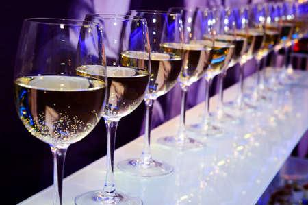 Nightclub Weingläser mit Weißwein von Partei festliche Lichter auf dunklem lila Hintergrund, Nachtbeleuchtung