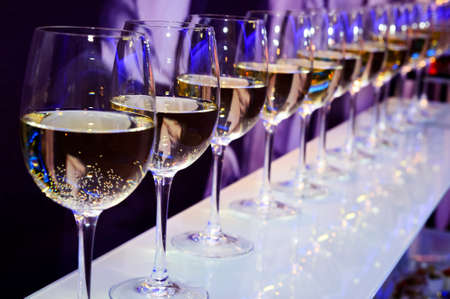 nightclub: Nightclub wine glasses with white wine lit by party festive lights on dark-purple background, nightlife