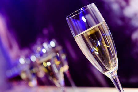 Luxury party champagne glass in nightclub neon lilac, blue and purple lights, nightlife, blurry closeup
