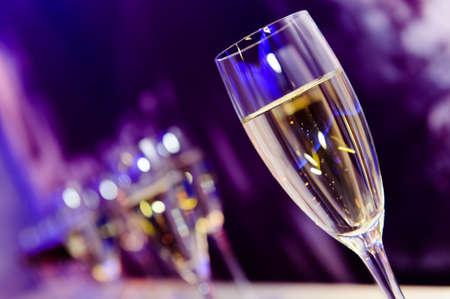 kutlama: Gece kulübü neon lila, mavi ve mor ışıklar, gece hayatı, bulanık closeup Lüks parti şampanya cam