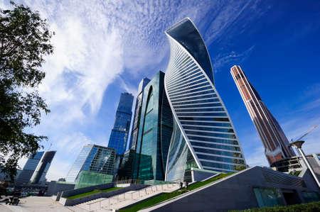 現代のビジネス オフィス高層ビル、商業地区、白い雲と青い空に上げるアーキテクチャで高層ビルを見上げて下ビュー