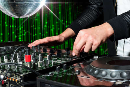 dance and electronic: DJ at dance party mixes track on sound mixer, nightclub with striped green interior and silver disco ball with star, professional stereo electronic equipment