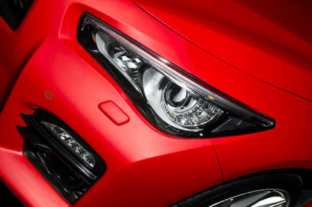Predatory car headlight and hood of powerful sports car with matte red paint and wheel with silver disc