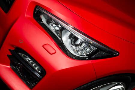 Räuberische Auto Scheinwerfer und Motorhaube des starken Sportwagens mit mattem roter Farbe und das Rad mit Silberscheibe Lizenzfreie Bilder