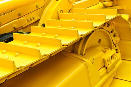 Bulldozer-Tracks und das Antriebszahnrad mit Ritzel-Mechanismus, große Baumaschine mit Schrauben und gelbe Lackierung, Schwerindustrie, Detail