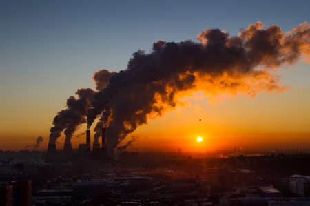 Power plant pipes with swirling smoke at sunrise, environmental pollution, view against the sun Stock Photo