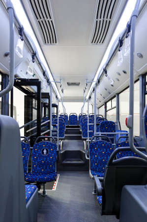 Bus inside, city transportation white interior with blue seats in row, retirement places, open doors, handles for standing passengers, bright lights and air conditioner 免版税图像