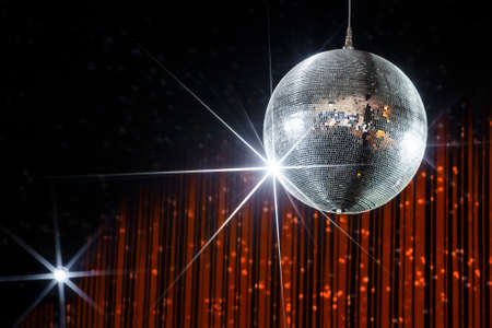 new ball: Disco ball with stars in nightclub with striped orange and black walls lit by spotlight, party and nightlife entertainment industry Stock Photo