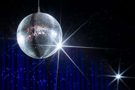 Disco ball with stars in nightclub with striped blue and black walls lit by spotlight, party and nightlife entertainment industry