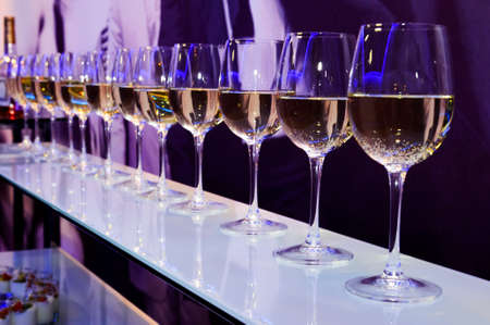 nightclub bar: Nightclub wine glasses with white wine lit by party festive lights on dark-purple background, nightlife