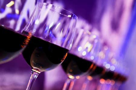 nightclub: Nightclub wine glasses with red wine lit by party festive lights on dark-purple background, nightlife