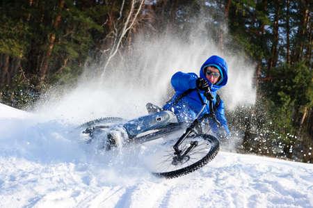 jinete: bicicleta de montaña extrema ciclista en la nieve que volaba cerca de bosque de invierno en día frío soleado