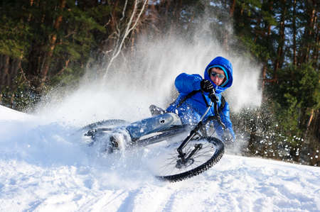 Cyclist extreme riding mountain bike in flying snow near winter forest in sunny cold day