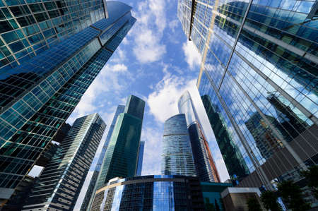 Modern business office skyscrapers, looking up at high-rise buildings in commercial district, architecture raising to the blue sky with white clouds, bottom view Фото со стока