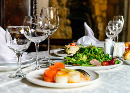 Served for holiday banquet restaurant table with dishes, snack, cutlery, wine and water glasses. European food Standard-Bild