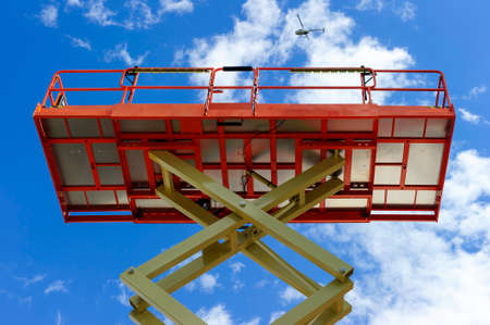 hydraulic lift: Scissor lift platform with hydraulic system at maximum height range painted in orange and beige colors, large construction machine, heavy industry, white clouds and blue sky on background