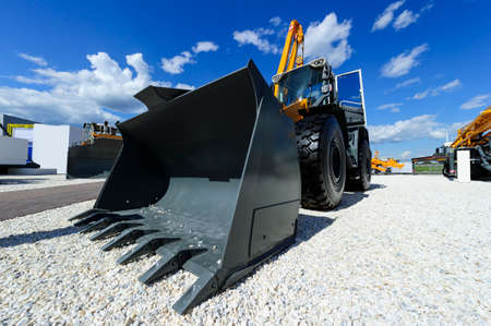 Loader, wheel bulldozer with big grey bucket, construction industry, heavy yellow excavator on building area with gravel, different machinery, blue sky and white clouds on background